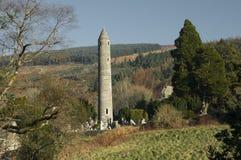 Rund torn och kyrkogård i Glendalough Arkivfoton