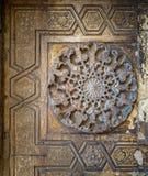 Runda blom- modeller som inramades av geometriska modeller, sned in i den yttre väggen av Sultan Hasan Mosque, Kairo, Egypten Royaltyfri Bild