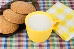 Runda bruna kakor i svart maträtt och kopp av mjölkar Royaltyfri Foto