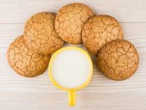 Runda bruna kakor in och koppen av mjölkar på tabellen Arkivfoton