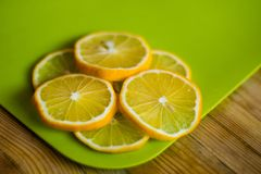 Runda citronskivor på en grön skärbräda på en trätabell royaltyfri fotografi