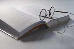 Runda de gamla exponeringsglasen lägger på en öppen vit bok, som ligger på en vit bakgrund royaltyfri fotografi