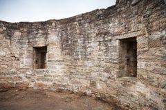 Runda den förstörda inre med tomma fönster av det gamla stenfortet Arkivbild