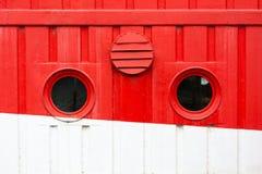 Runda fönster på det röda och vita kryssningskeppet royaltyfria foton