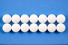 Runda farmaceutiska preventivpillerar för vit på blå bakgrund Royaltyfria Bilder