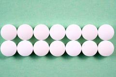 Runda farmaceutiska preventivpillerar för vit på grön bakgrund Royaltyfri Bild