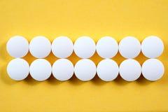Runda farmaceutiska preventivpillerar för vit på gul bakgrund Arkivbild