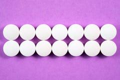 Runda farmaceutiska preventivpillerar för vit på rosa bakgrund Arkivbild