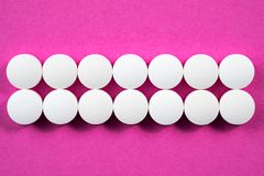 Runda farmaceutiska preventivpillerar för vit på rosa bakgrund Fotografering för Bildbyråer