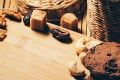 Runda frasiga chokladkakor med kryddor och muttrar på en tabell, Arkivfoto