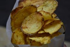 Runda frasiga gula potatischiper i den vita påsecloseupen royaltyfri foto