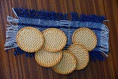 Runda kakor på en ullservett på en brun tabell Fotografering för Bildbyråer