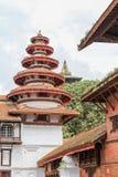 Runda mång--tiered torn i nasala Chowk med den Taleju templet som precis är synlig i bakgrunden Durbar fyrkant, Katmandu Royaltyfri Fotografi