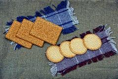 Runda- och fyrkantkex ligger på den woolen torkduken Royaltyfri Bild