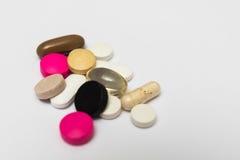 Runda preventivpillerar och ovala hårda och mjuka kapslar på vit bakgrund Royaltyfri Fotografi