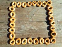 Runda små frasiga baglar som ligger på en trätabell Royaltyfri Foto