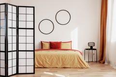 Runda svarta ramar på den vita väggen av den eleganta sovruminre med konungformatsäng med gul och ljust rödbrun sängkläder royaltyfri fotografi