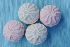 Runda vita rosa marshmallower på en blå tabell Arkivbild
