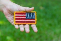 Rundad amerikanska flagganlapp för hand innehav royaltyfria bilder