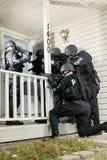 Rundar det samlade taktiska laget för polisen ett hus royaltyfri bild