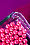 Rundarosa färg pryder med pärlor i den Glass maträtten Royaltyfri Bild