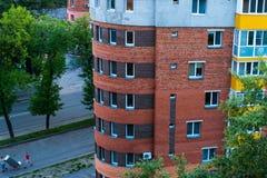 Runde Eckdraufsicht des Gebäudes mit Straße und Leute und Fenster Lizenzfreies Stockbild