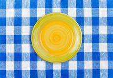 Runde gelbe Platte auf überprüfter Tischdecke Lizenzfreies Stockfoto