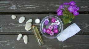 runde Kiesel des Badekurortes Seeund rosa Blumen auf hölzernem Hintergrund lizenzfreies stockbild