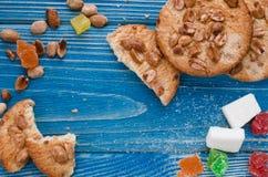 Runde orange Kekse mit bunten kandierten Früchten und eine Scheibe der saftigen Orange liegend auf einem Holztisch lizenzfreie stockfotografie