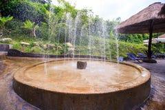 Runde Steinbrunnen-Jets durch Reed Umbrella im Park Stockfotos
