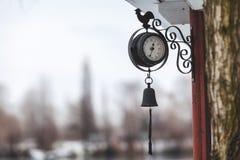 Runde Uhr der Straße mit Glocke und Hahn Stockbild