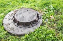 Runder Abwasserkanalkanaldeckel im grünen Gras Lizenzfreie Stockfotografie
