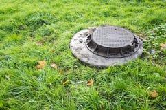 Runder Abwasserkanalkanaldeckel im grünen Rasen Stockfoto