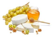 Runder Briekäse oder camambert Käse und Honig staut auf einem weißen Hintergrund Stockfotografie