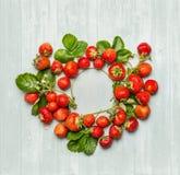 Runder Kreisrahmen von Erdbeeren mit Grünblättern und -blumen auf hölzernem Hintergrund, Draufsicht Stockfotos