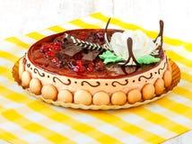 Runder Kuchen mit Kirsche und Keksen auf Tischdecke Stockbilder