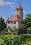 Runder mittelalterlicher Turm mit Sonnenblumen-Garten stockfotografie