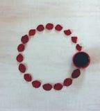 Runder Rahmen von Blumenblättern des Scharlachrots Rose und Tasse Kaffee auf grauem Schmutzhintergrund mit Raum für Text Lizenzfreies Stockfoto
