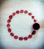 Runder Rahmen von Blumenblättern des Scharlachrots Rose und Tasse Kaffee auf grauem Schmutzhintergrund mit Vignette mit Raum für  Lizenzfreies Stockbild