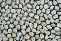 Runder Stein auf dem schwarzen Boden Stockfotos
