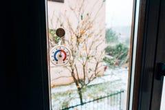 Runder Thermometer auf dem Fenster 5 Grad Celsius Der Schnee heraus Stockfotos