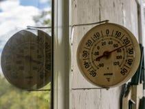 Runder Thermometer reflektiert im Fenster an einem Sommertag lizenzfreies stockbild