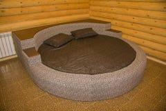 Rundes Bett in einem hölzernen Schlafzimmer Lizenzfreie Stockfotografie