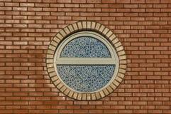 Rundes Fenster auf Backsteinmauer Lizenzfreies Stockfoto