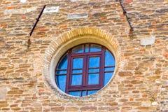 Rundes Fenster auf Backsteinmauer Stockbild
