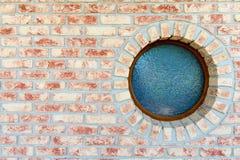 Rundes Fenster auf Backsteinmauer Lizenzfreie Stockfotos