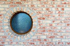 Rundes Fenster auf Backsteinmauer Stockbilder