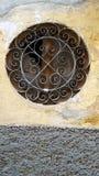 Rundes Fenster in der Steinwand mit Metallgrill lizenzfreie stockfotos