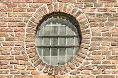 Rundes Fenster in einer alten Backsteinmauer Stockfoto