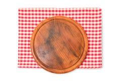 Rundes hölzernes Brett mit der überprüften Tischdecke lokalisiert auf weißem Hintergrund Lizenzfreies Stockbild